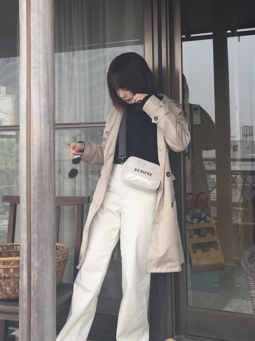 トレンチコートとスウェットプルオーバーにワイドパンツを履いた女性