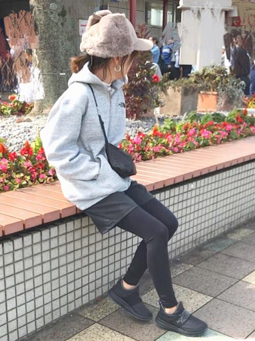 ノースフェイスのフルジップパーカーとシンプルパンツにライトモックを履いた女性