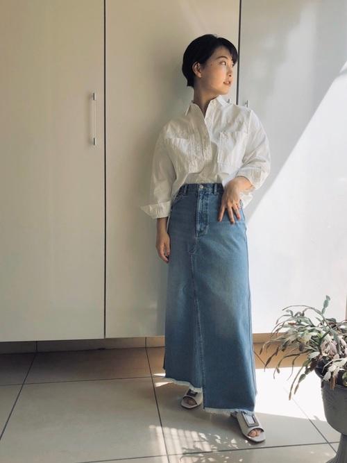 オーバーシャツとフロントラップデニムスカートにスライドサンダルを履いた女性