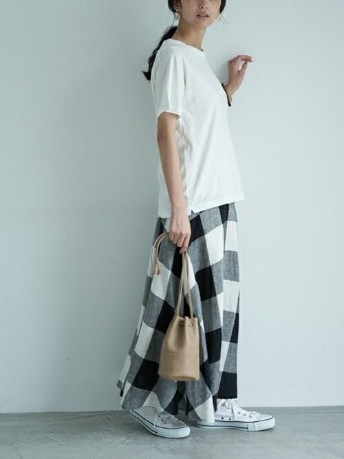ブロックチェックロングマーメイドスカートにクルーネックTシャツを着た女性