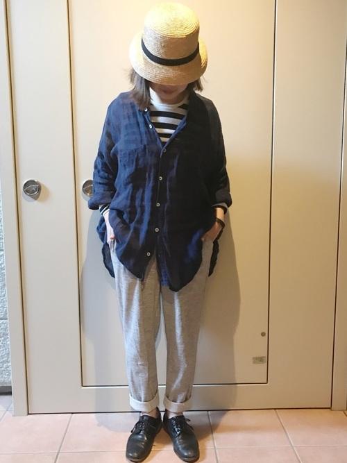 ストローハットとボーダーシャツにトリッカーズシューズを履いた女性
