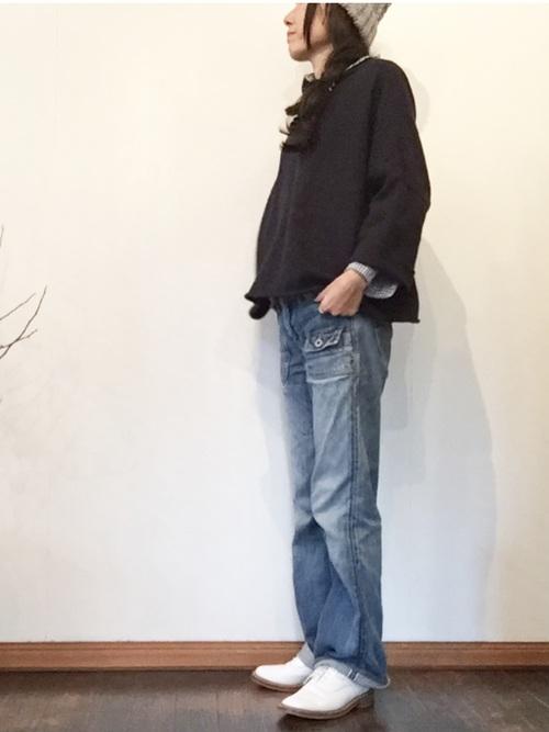 デニムパンツとブラックジャケットにトリッカーズシューズを履いた女性