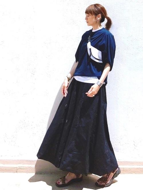 ネイビードライカイトTシャツとネイビーバルーンスカートにカーキスポーツサンダルを履いた女性