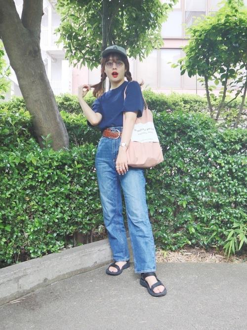 ネイビークロップドクルーネックTシャツとストレートデニムパンツに黒バンドサンダルを履いた女性