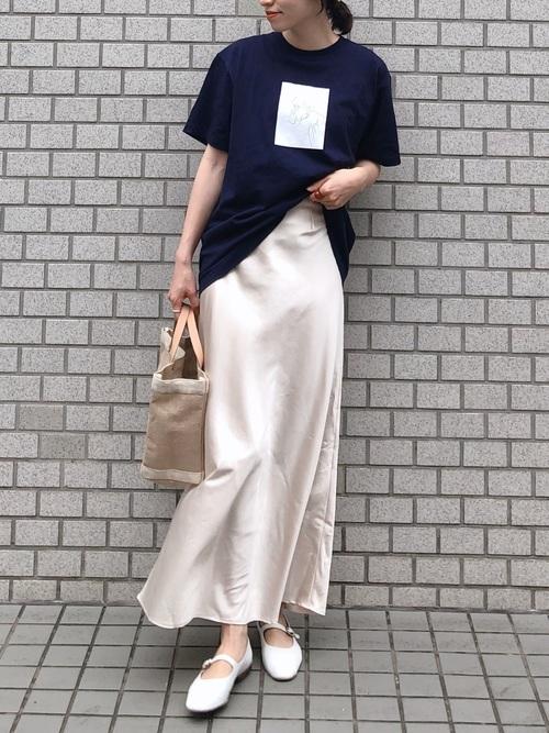 ネイビープリントクルーネックTシャツとベージュサテンスムーススカートに白ストラップシューズを履いた女性