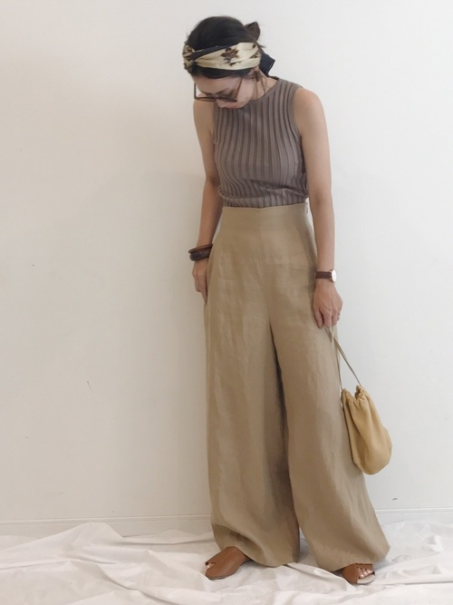 ブラウンニットタンクトップにベージュハイウエストリネンパンツを履いた女性