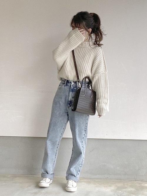 ホワイトニットにハイウエストデニムパンツを履いた女性