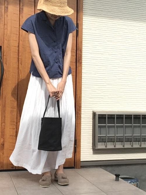 白ギャザーロングスカートとネイビーテーラー襟シャツにベージュタッセルモカシンを履いた女性