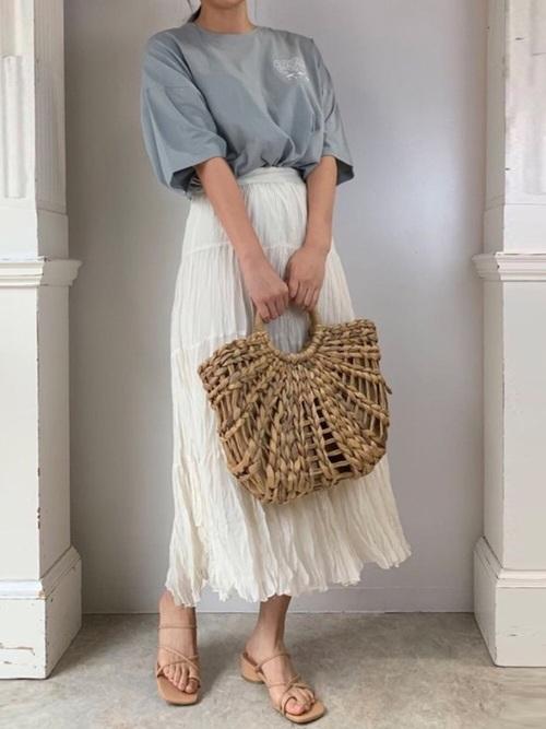 白クリンクルロングスカートとブルーバッグレタリングプリントビッグTシャツにベージュトングサンダルを履いた女性
