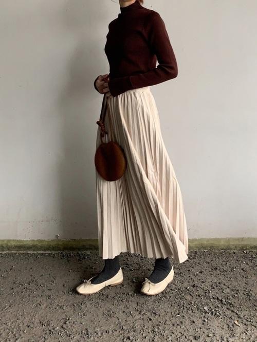 白プリーツスウェードロングスカートとブラウンロールアップスリーブリブハイネックニットに白バレエシューズを履いた女性