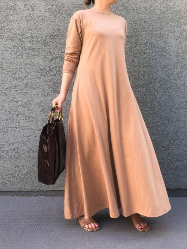 ベージュピンクのカットソーワンピースにしまむらのクリアバッグを持った女性