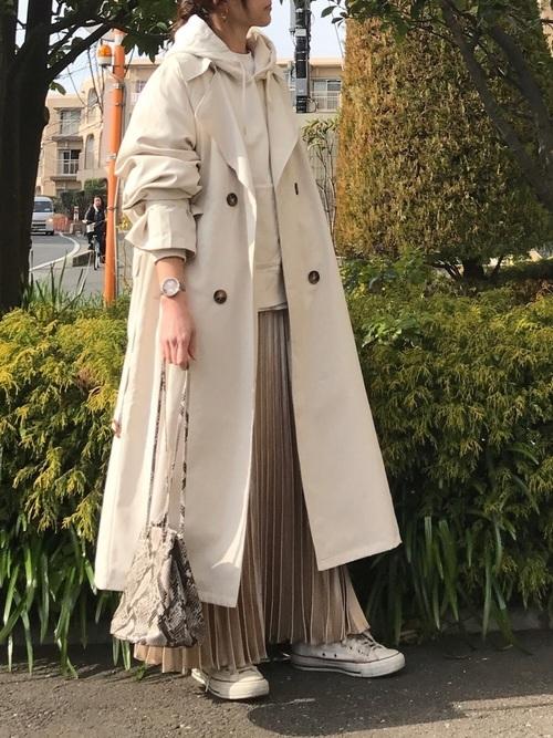 ベージュスウェットパーカーにプリーツスカートを履いた女性