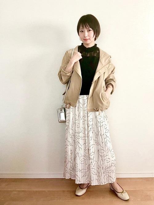 ベージュマウンテンパーカーにプリーツスカートを履いた女性