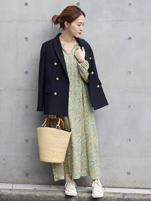 紺テーラードダブルジャケットとロングワンピースに白スニーカーを履いた女性