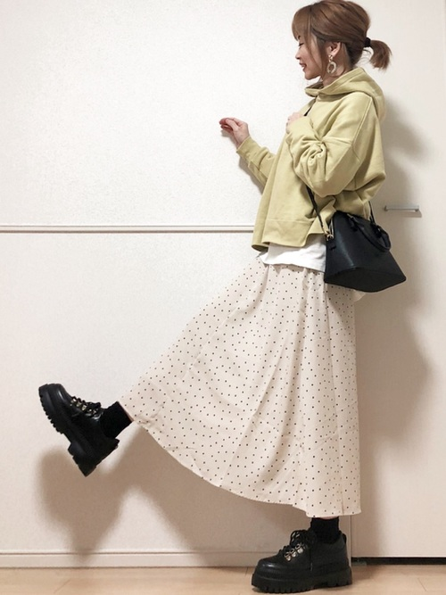 薄黄色コットンワイドプルオーバーパーカーと水玉Aラインロングスカートに厚底マウンテンシューズを履いた女性