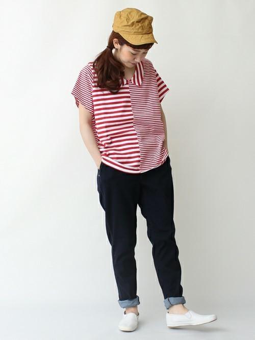 赤クレイジーボーダープルオーバーにストレッチデニムパンツを履いた女性