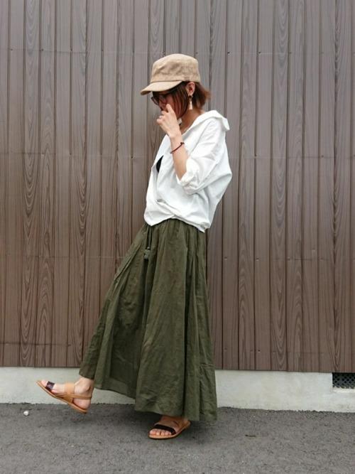 白ビッグシャツにカーキロングフレアスカートを履いた女性