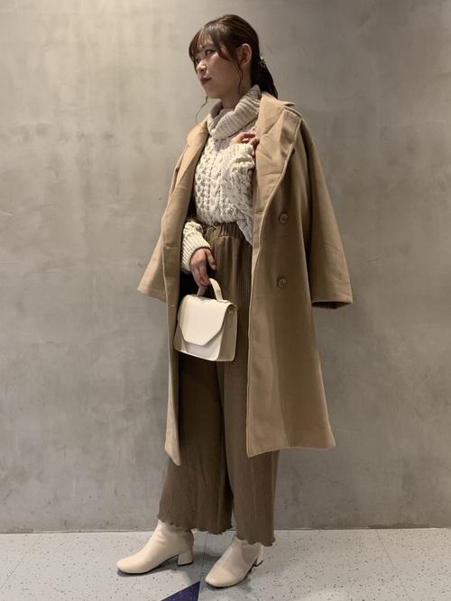 ベージュコートとベージュワイドパンツにホワイトニットを履いた女性