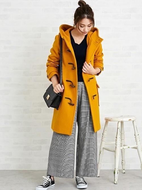 イエローダッフルコートとグレンチェックパンツにスニーカーを履いた女性