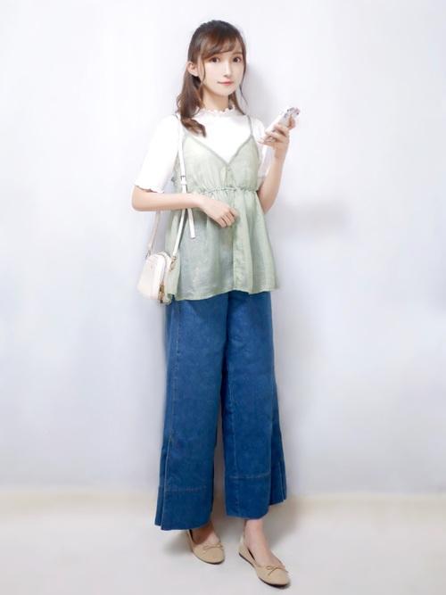 ミントグリーンキャミソールとデニムフレアパンツにパンプスを履いた女性