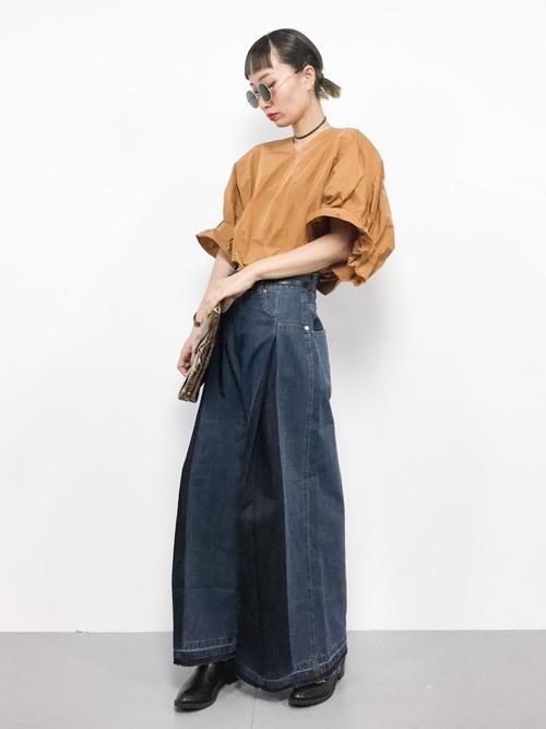 インディゴデニムワイドパンツとボリュームスリーブブラウスにゴールドクラッチバッグを履いた女性