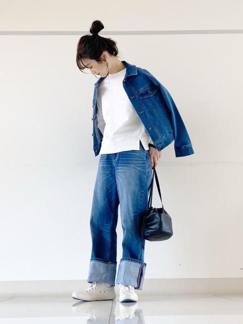 ブルーデニムワイドパンツと白ボリュームスリーブスウェットプルオーバーにブルーデニムGジャンを履いた女性