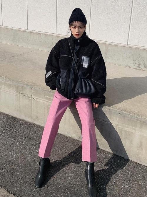 ボアジャケットにピンクテーパードパンツを履いた女性