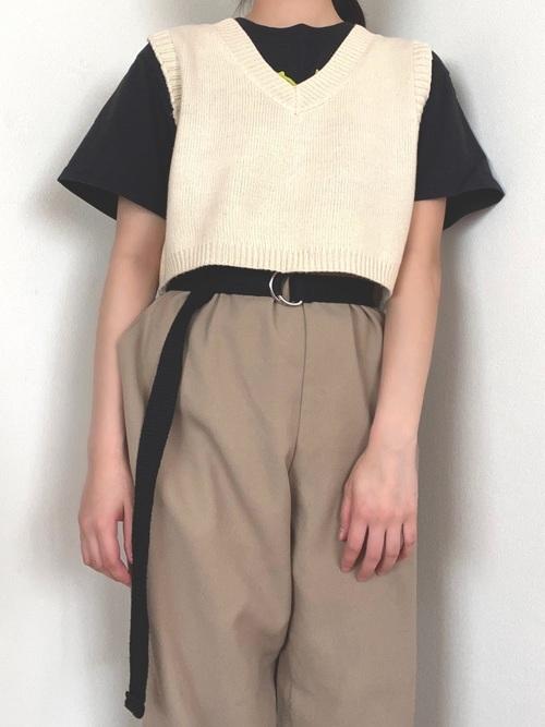 スピンズニットベストとスピンズTシャツにベージュチノパンを履いた女性
