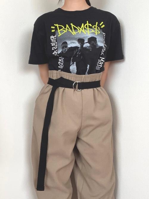 スピンズTシャツとベージュチノパンにベルトを履いた女性