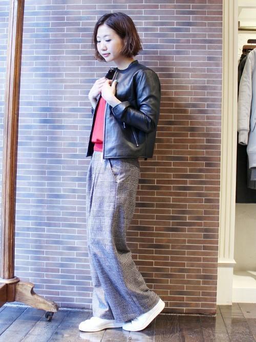 黒シングルライダースジャケットと赤Vネックプルオーバーにチェック柄ワイドパンツを履いた女性