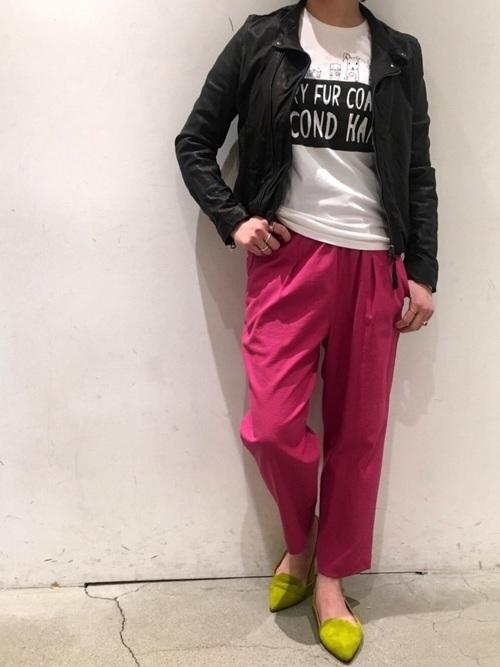 黒シングルライダースジャケットと白プリントTシャツにピンククロップドパンツを履いた女性