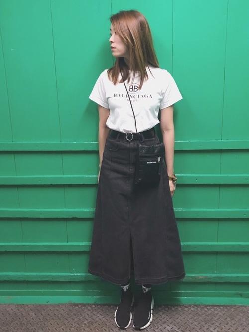 ダブルBロゴTシャツにロングデニムスカートを履いた女性