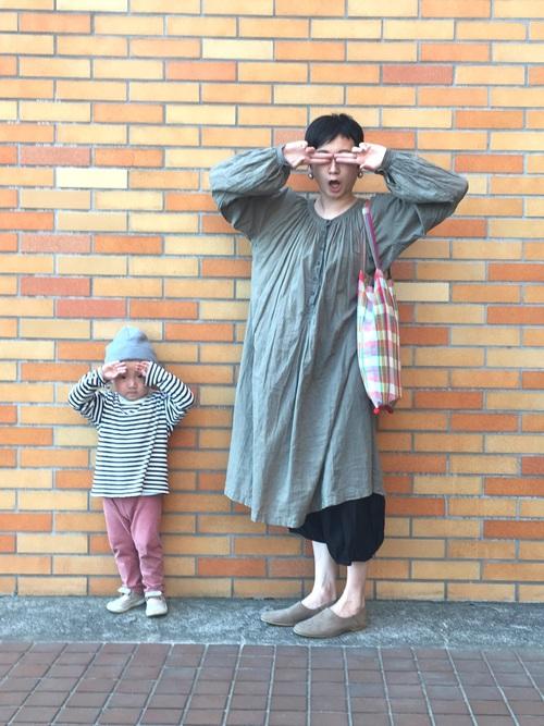 グリーンギャザーフレアワンピースとベージュスリッポンにピンクチェックトートバッグを持った女性