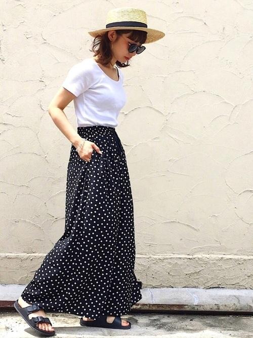 黒デシンドット柄ワイドパンツと白UネックTシャツにカンカン帽を履いた女性