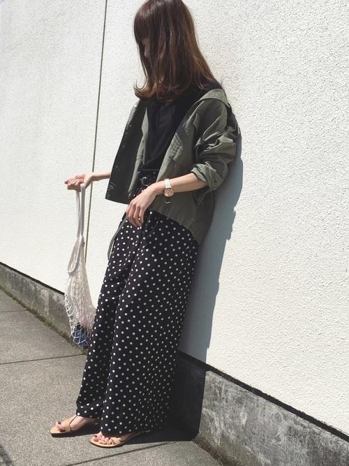 黒ドット柄トシャーリングワイドパンツとカーキコットンミリタリーシャツにベージュストラップサンダルを履いた女性