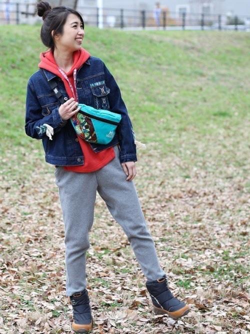 チチカカのデニムジャケットとオレンジプルパーカーにグレージャージーパンツを履いた女性
