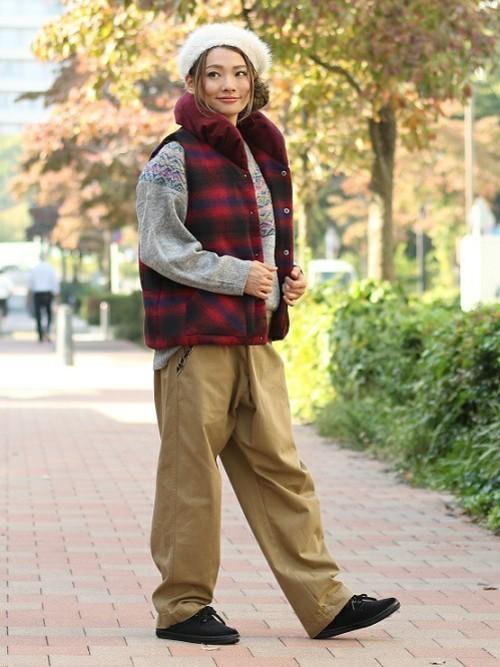 チチカカの中綿ベストとグレーニットセーターにワイドチノパンツを履いた女性