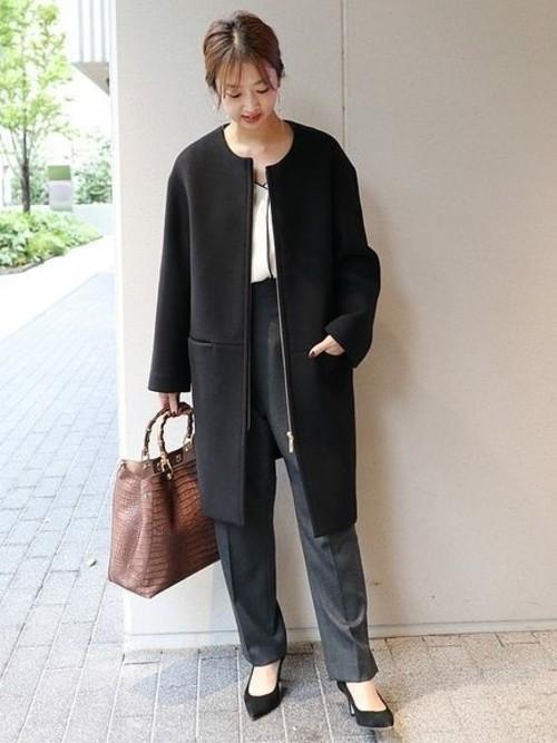 グレースラックスと黒ノーカラーコートに黒パンプスを履いた女性