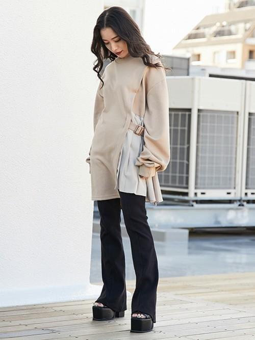 厚底ストラップサンダルとハーフプリーツワンピースにフレアパンツを履いた女性