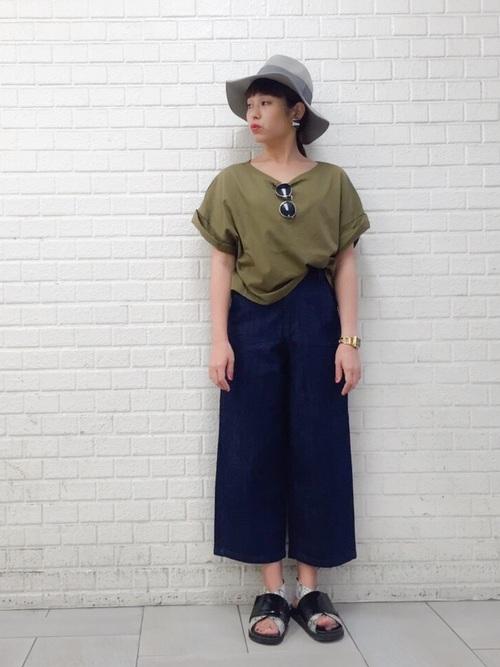 緑ロールスリーブTシャツとインディゴクロップドワイドデニムパンツに黒コンビサンダルを履いた女性