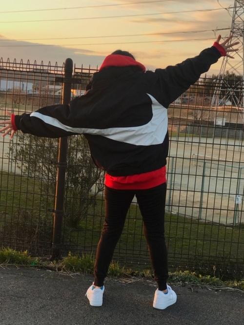 ナイキのアノラックジャケットと赤スウェットパーカーにブラックスキニーパンツを履いた女性