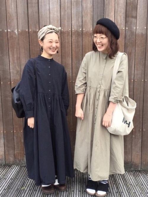スタンドカラーシャツワンピースとリブボーダーソックスにトートバッグを持った女性