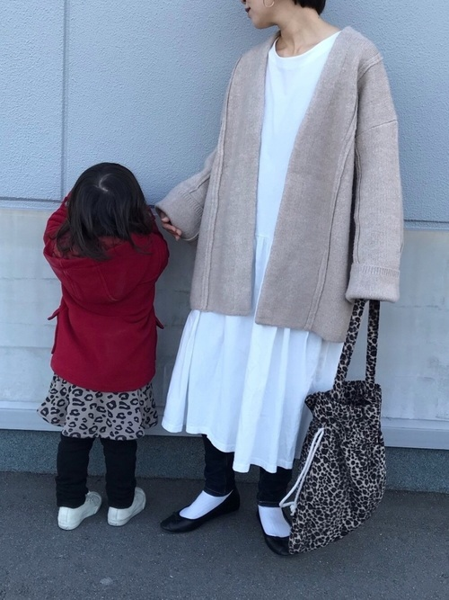 ニットコートと白ワンピースにレオパード柄バッグを履いた女性