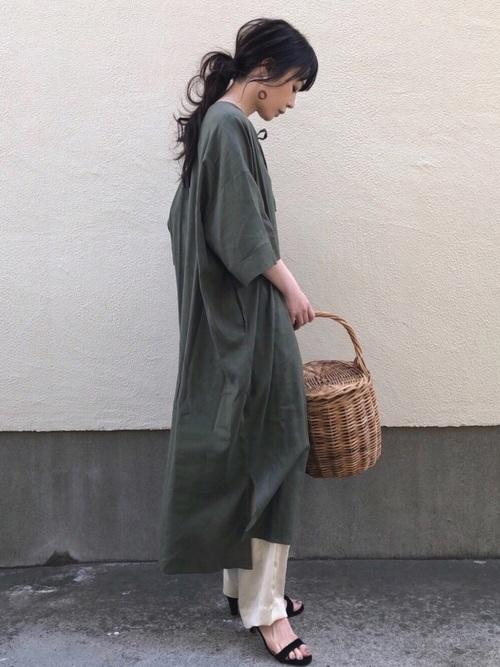 グリーン五分袖カフタンワンピースに白サテンラインパンツを履いた女性