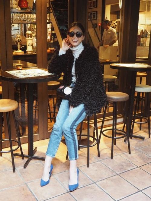 ブルーデニムサイドラインキャロットパンツに黒フェイクファージップアップジャケットを着た女性