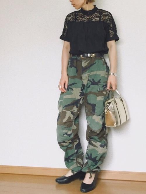 迷彩カーゴパンツにレースカットソーを着た女性