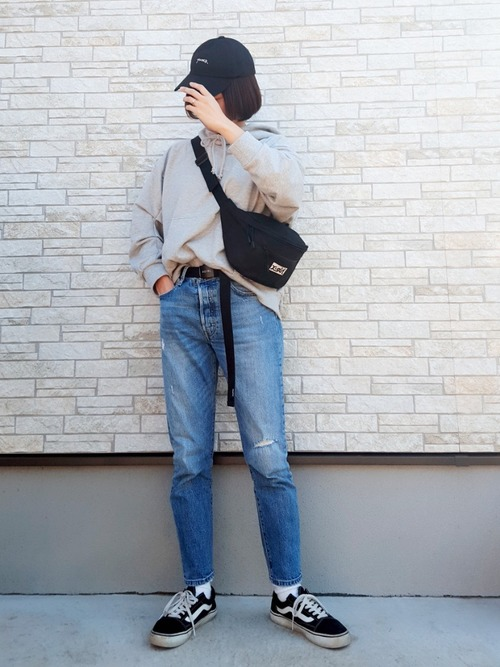 グレーフーディにスキニーデニムパンツを履いた女性