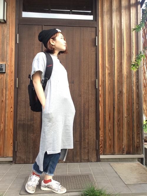 ロングTシャツワンピースにデニムパンツを履いた女性