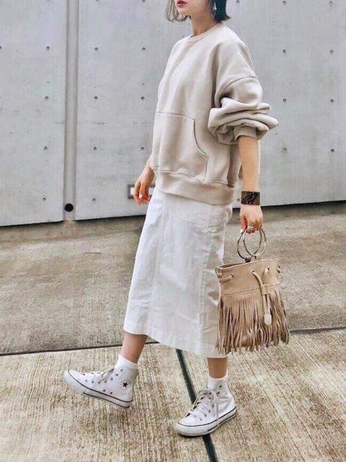 オフホワイトマフポケットスウェットとホワイトミリタリータイトスカートにホワイトハイカットスニーカーを履いた女性