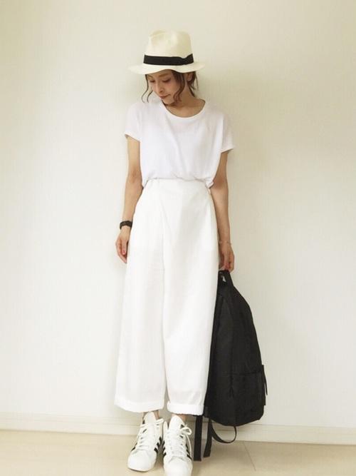 ホワイトワイドクルーネックTシャツとホワイトラップパンツにホワイト中折れハットを履いた女性
